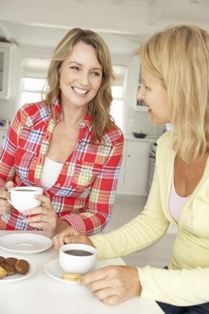 mujer tomando cafe: Mujeres de mediana edad charlando con un café en su casa