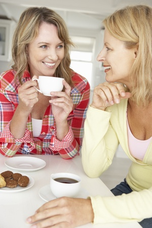 Mid age women chatting over coffee at home photo