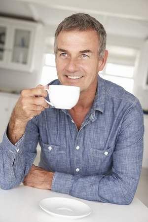greying: Mid age man with coffee at home Stock Photo