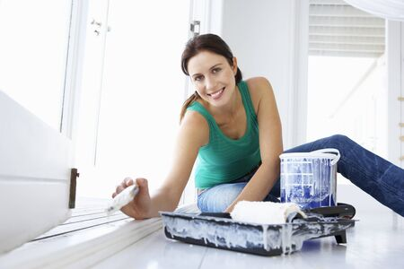 renovating: Woman decorating house Stock Photo