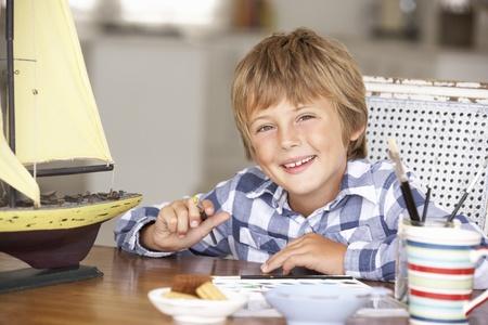 Young boy making model ship photo