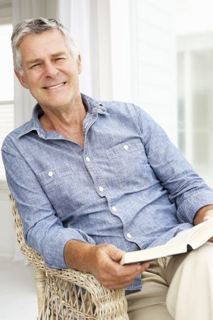 Senior man relaxing at home with a book photo