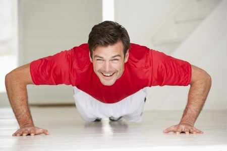 home keeping: Man doing push-ups in home gym Stock Photo