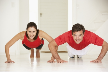 home keeping: Couple doing push-ups in home gym