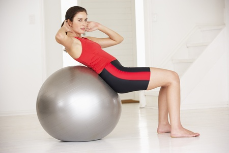 home keeping: Woman with gym ball in home gym