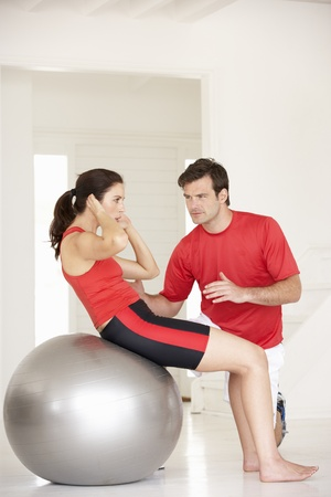 Woman with personal trainer in home gym photo