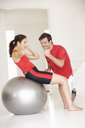 abdomen plano: Mujer con entrenador personal en el gimnasio en casa Foto de archivo