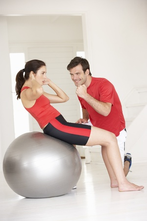 home keeping: Woman with personal trainer in home gym