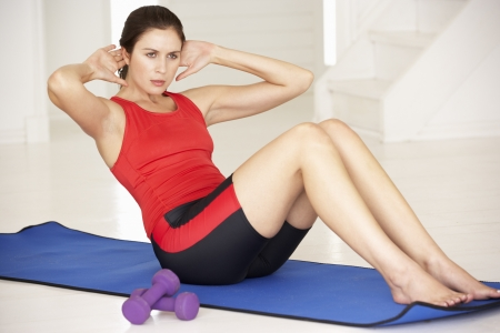 home keeping: Woman doing sit-ups in home gym