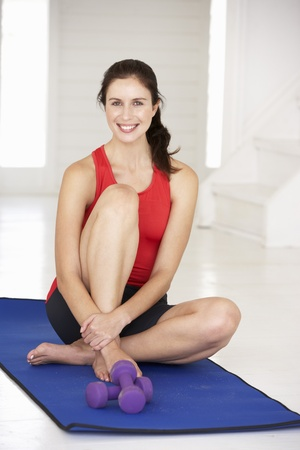 Woman sitting on exercise mat photo