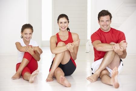 family exercise: Mother,father and daughter doing yoga