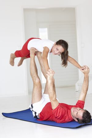 Father and daughter doing yoga lift photo