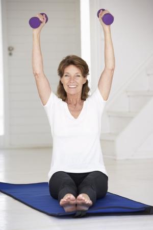 levantando pesas: Mujer mayor ejercicio en casa Foto de archivo