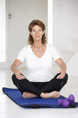 Senior woman sitting in lotus position photo