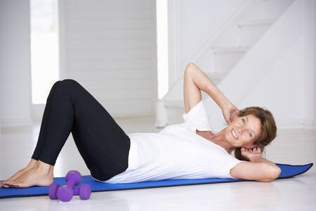 home keeping: Senior woman doing curl-ups Stock Photo