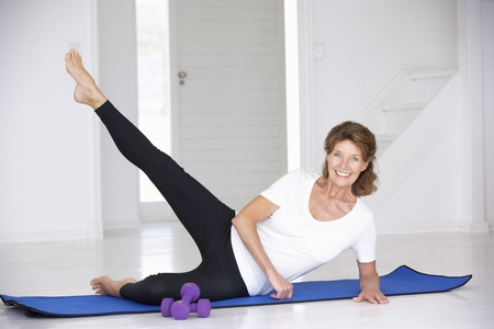 Senior woman exercising in home gym photo