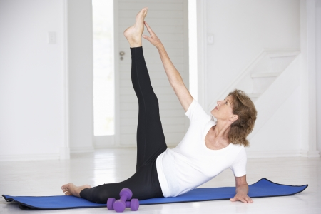 fits in: Senior woman exercising in home gym