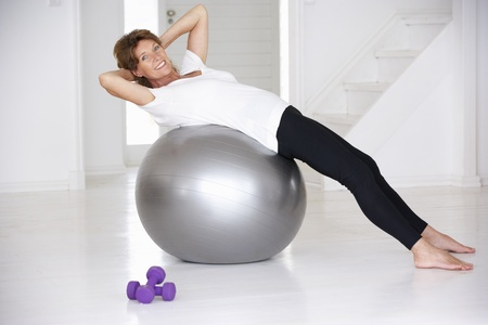 fits in: Senior woman using gym ball