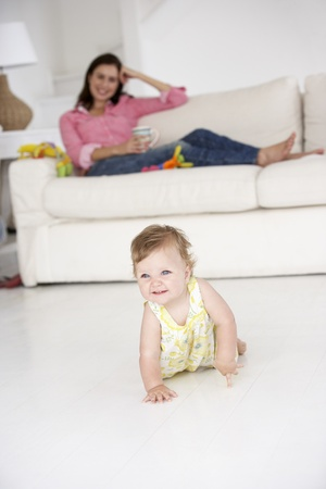 Mother watching baby crawl photo