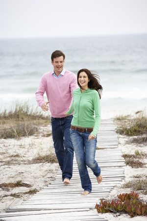 Couple running along beach path photo