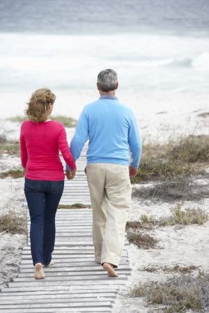 ancianos caminando: Senior pareja caminando por el mar