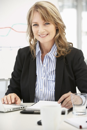40s: Mid age businesswoman at work Stock Photo