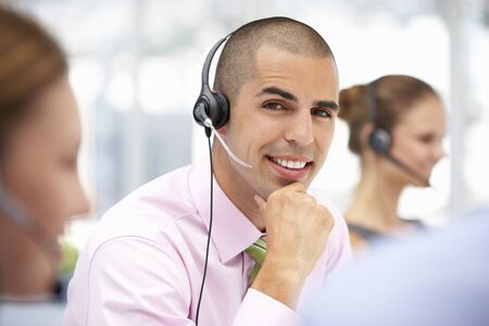 call centre: Young businessman wearing headset