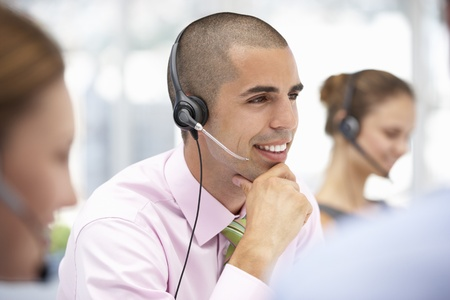 business centre: Young businessman wearing headset