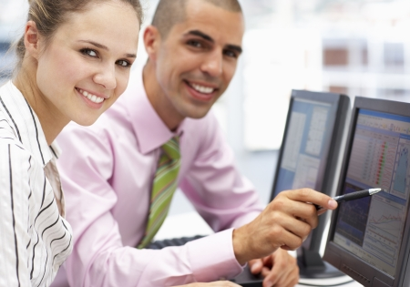com: Businessman and woman working on computers
