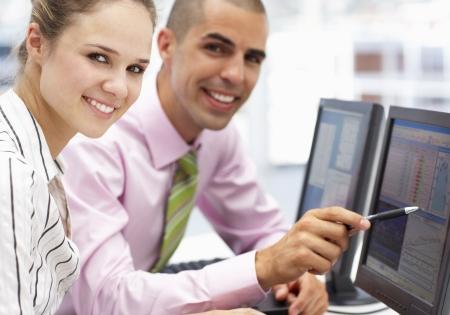 trabajando en computadora: Hombre de negocios y la mujer trabajando en las computadoras Foto de archivo