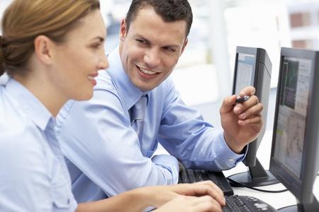 personas ayudandose: Hombre de negocios y mujeres trabajando en las computadoras Foto de archivo