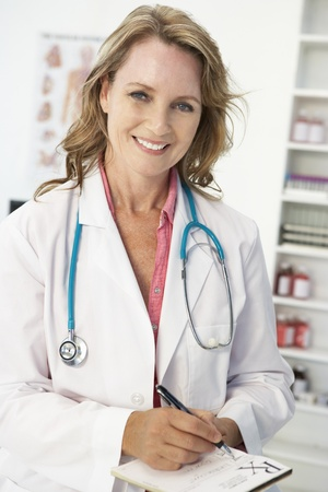 Mid age female doctor writing prescription photo