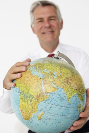 Senior businessman holding globe photo