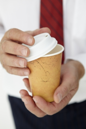 to go cup: Businessman holding takeout coffee