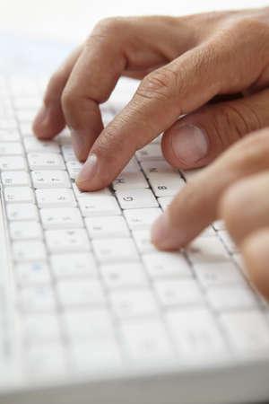 Close up man using computer keyboard photo