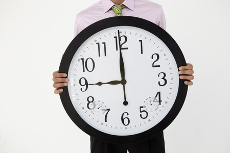ticking: Young businessman with giant clock Stock Photo