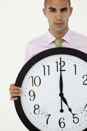Young businessman with giant clock photo