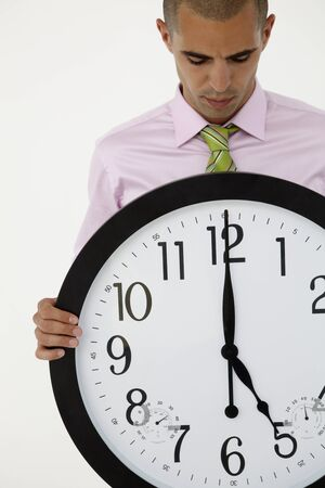 running out of time: Young businessman with giant clock Stock Photo
