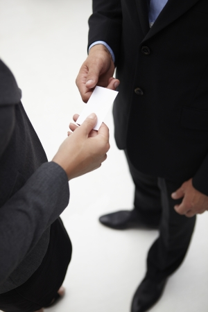Detail businessman and woman exchanging cards photo