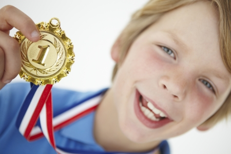 winning first: Young boy showing off medal