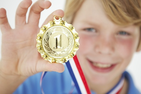 Young boy showing off medal