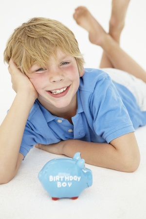 managing money: Young boy with piggy bank