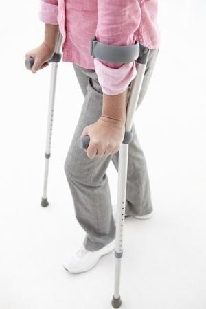 elleboog: Vrouw lopen met krukken Stockfoto
