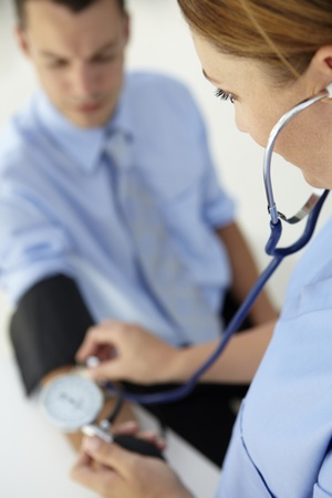 Doctor taking young man's blood pressure Stock Photo - 11211392