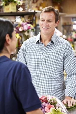 retailer: Man serving customer in florist