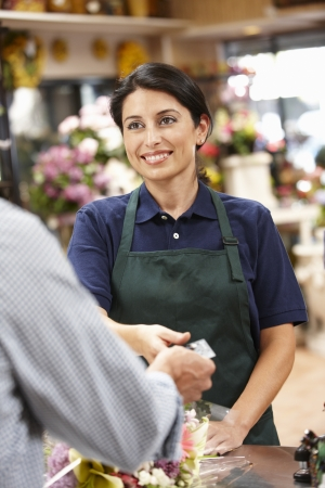 counter service: Woman serving customer in florist Stock Photo