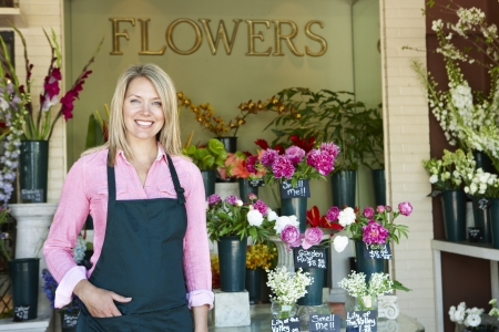 business owner: Woman standing outside florist