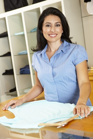 womens clothing: Hispanic woman working in fashion store