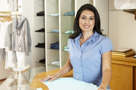 top clothing: Hispanic woman working in fashion store