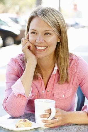 Woman sitting at sidewalk caf� photo